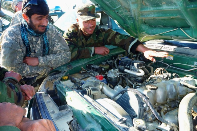 Afghan police attending the Up-Armored Humvee Light Tactical Vehicle Course look over the engine of a Ford Ranger pickup truck Feb. 8.