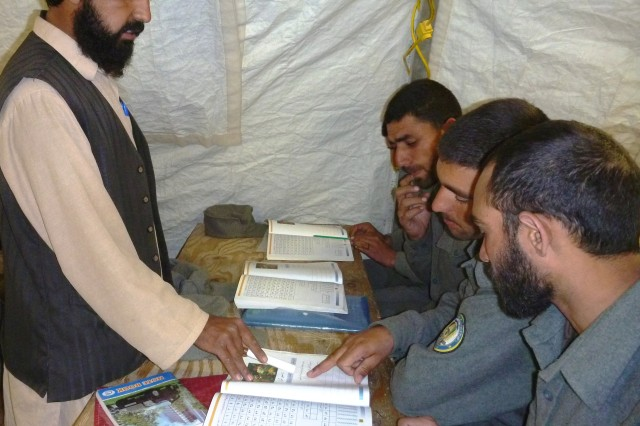 An Afghan teacher helps Afghan Uniformed Police recruits learn how to read in a literacy training class Feb. 9 at Spin Boldak (Costell) training sustainment site.