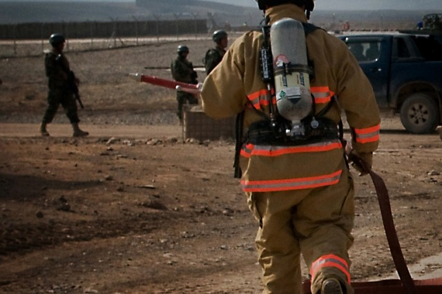 William Woods, a firefighter for the Tarin Kot Fire Department, extends a fire hose during a training exercise Feb. 19 while Afghan National Army soldiers look on at Multi-National Base Tarin Kot, Afghanistan. Woods is a Riverside Ca., native. (U.S. Army photo by Spc. Edward A. Garibay, 16th Mobile Public Affairs Detachment)