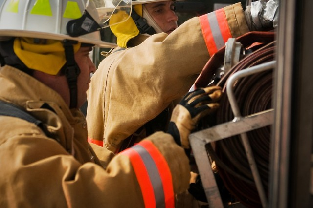 William Woods (Left) and Avery Hanoumis (Right), firefighters for the Tarin Kot Fire Department and Riverside, Ca., natives, pull equipment from their fire truck Feb. 19 at Multi-National Base Tarin Kot, Afghanistan. The truck was passed on to the U.S. firefighters in October when they took over the fire station  from the Dutch. (U.S. Army photo by Spc. Edward A. Garibay, 16th Mobile Public Affairs Detachment)