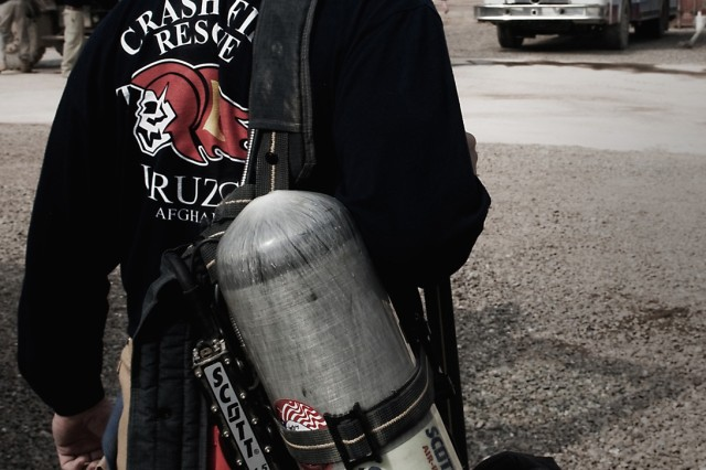 Michael Muston, a firefighter for the Tarin Kot Fire Department and Austin, Texas, native removes his equipment after a training exercise Feb. 19 at Mulit-National Base Tarin Kot, Afghanistan. The insignia on the back of Muston's shirt is a rendition of the insignia used by the Dutch fire department before the U.S. took over in October. The insignia continuity  is a way to pay homage and carry on tradition said George J. Chambers III, chief of the TKFD and Hillsboro, Tenn., native. (U.S. Army photo by Spc. Edward A. Garibay, 16th Mobile Public Affairs Detachment)