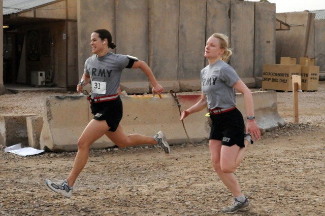 "Capt. Nicole Hall and Capt. Catherine Hamilton, both of Regimental Headquarters and Headquarters Troop, 3rd Armored Cavalry Regiment, dash through the finish line of the Livestrong Austin Marathon and Half Marathon ""shadow run"" held on Contingency Operating Site Kalsu, Iraq, Sunday. The race was held to support morale for the Soldiers, Airmen, and civilians who participated and was sponsored by the Austin Marathon."