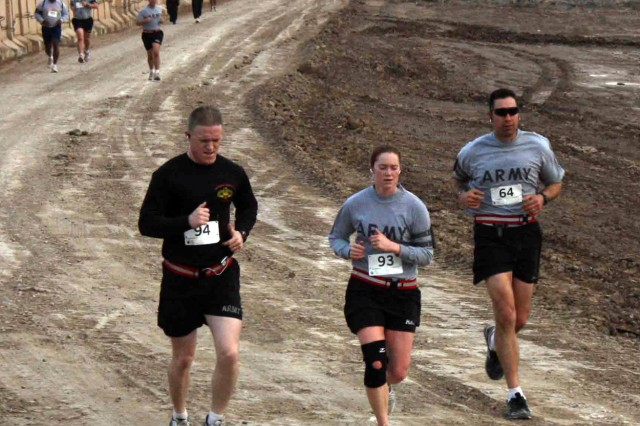 "Runners competing in the Livestrong Austin Marathon and Half Marathon ""shadow run,"" round a bend in the course on Contingency Operating Site Kalsu, Iraq, Sunday. The three lap, 13.1-mile course followed the perimeter of the base and consisted of concrete walls and a gravel trail, in contrast to the paved roads and green trees of Austin, Texas. The Austin Marathon sponsored the race with shirts, medals, and a finish line banner."