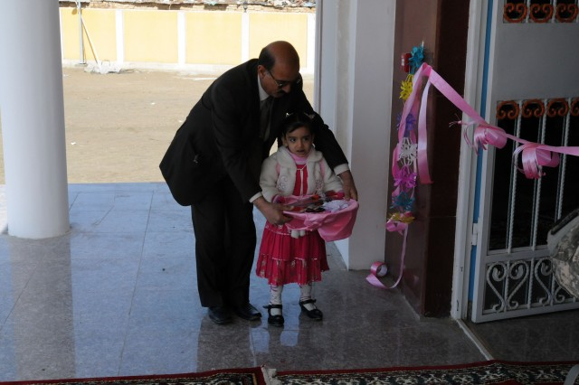 021211-A-6043A-013- A girl and her grandfather prepare to receive guests at the Musayyeb, Iraq Civic Center opening. The center is the largest of its kind in the Babil Province. (photo by Staff Sgt. Mark Albright)