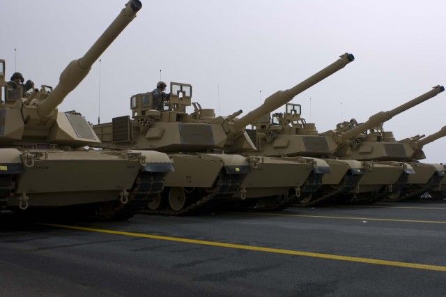 CAMP ARIFJAN, KUWAIT - A row of tanks, manned by Kuwaiti Soldiers, roll through the street during rehearsals for the 50/20 parade in Kuwait, Feb. 21. The 50/20 celebration honors the liberation of Kuwait as well as the spirit of unity forged during Operations Desert Storm and Desert Shield.  This celebration honors the Veterans of Operation Desert Storm and recognizes the long standing and successful partnership that is indicative of our many friendships in the region.