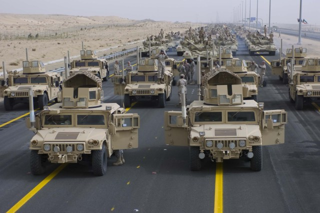 A formation of armored vehicles, manned by U.S. Army and Marine Corps personnel, stand ready to lead a convoy of coalition forces through the parade grounds established for the 50/20 celebration in Kuwait, Feb. 21.