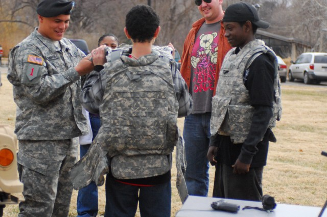 Pvt. Richard Hernandez of Co. C., 1st Bn., 28th Inf., 4th IBCT, assists individuals trying on military body armor on Kansas State University's campus Feb. 20. Soldiers of the 'Black Lions' provided a display of military vehicles and weapons in honor of Military Appreciation Day at the 55th Annual KSU Collegiate Rodeo.