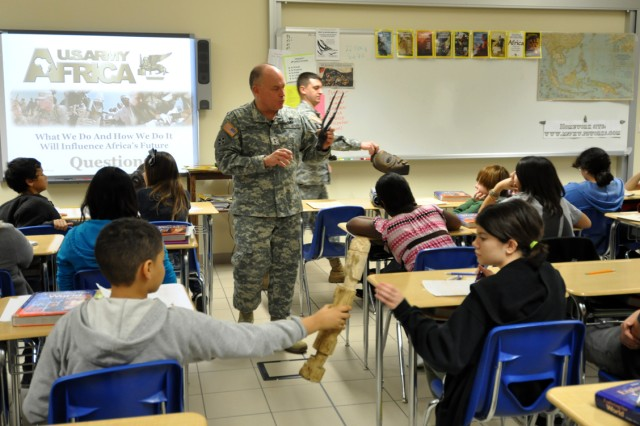 World geography students at Vicenza Middle School in Vicenza, Italy, pass and examine African artefacts while U.S. Army Africa Commander, Maj. Gen. David R. Hogg, discusses the interrelatedness of geography and history during a visit to the school Feb. 22, 2011.""