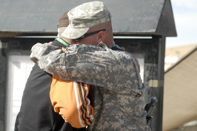 CAMP BUEHRING, Kuwait- Pfc. Brandon Albert (right), from C Company, 3rd Brigade Special Troops Battalion, 3rd Advise and Assist Brigade, 1st Cavalry Division, hugs his father Henry Albert, a civilian contractor at Camp Arifjan, at Camp Buehring Feb. 15 after being away from each other for three years.