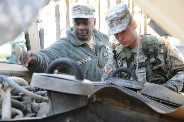 Staff Sgt. Burley Kessler and Pfc. Robert Duley, Company B, 187th Ordnance Battalion, check the engine of a humvee before embarking on a convoy operations exercise Feb. 15 at the 187th Field Training Exercise site. The new scenario-based training is aimed at improving leadership and Soldier skills.