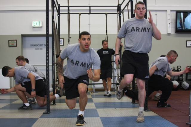 Retired Navy SEAL and TRX trainer Ken Taylor monitors in the background while Pfc. Derrick Bales, left, and Pfc. Kyle Chubboy, right, break a sweat using their TRX strap. The TRX training is part of the Mission Essential Fitness pilot program being tested on 1-91 Soldiers in Schweinfurt.