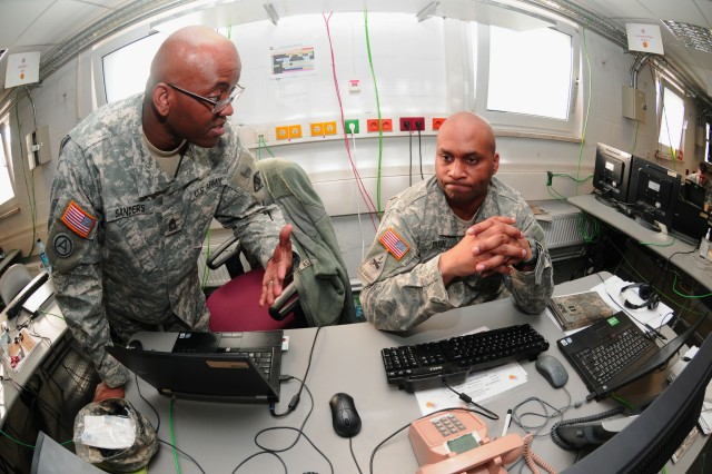 GRAFENWOEHR, Germany (February 23, 2011) - Master Sgt. Charlie Sanders (left) provides an update on a Mission Event Synchronization List to Capt. Lashon Bush in the Joint Cyber Control Center during Operation Deuce Lightning. Sanders and Bush are among more than 60 U.S., German Soldiers and Airmen who are participating in the exercise Feb. 1 to Mar. 4 in order to assess the Brigade's ability to provide a robust, flexible and reliable network, with the brigade headquarters acting as the core of the JCCC. Sanders is the Network Operations non-commissioned officer in charge and Bush is the NETOPS officer in charge.(Official U.S. Army Photo by Lawrence Torres III)(released)