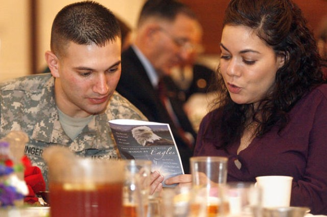 """Sgt. Jason Spahlinger, a chaplain\'s assistant with Headquarters Command Battalion, and his wife, Tania, the executive assistant to Deputy Installation Commander John Moeller, sing """"My Country 'Tis of Thee"""" at the installation's National Prayer Luncheon held Feb. 17 at Club Meade."""