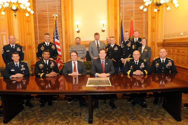Sam Brownback, governor of Kansas, poses for a photo with military and community leaders from around the state before signing the Army Community Covenant at the capitol building in Topeka, Kan., Feb. 24. The signing was held as part of the Kansas Military Appreciation Day proceedings.