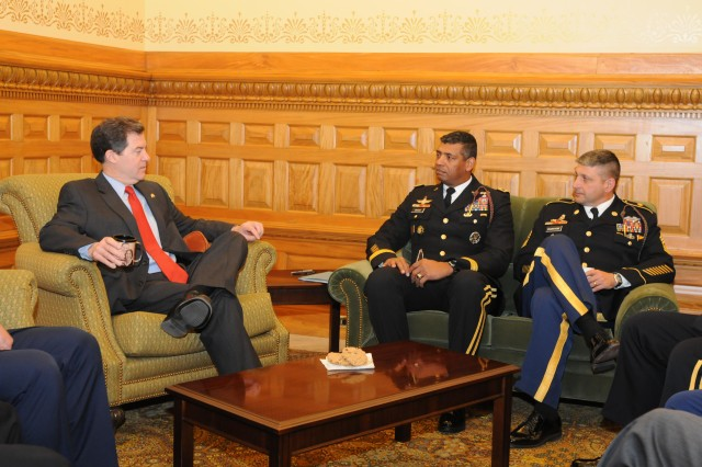 Sam Brownback, governor of Kansas, talks with Maj. Gen. Vincent Brooks and Command Sgt. Maj. Jim Champagne, the commanding general and senior noncommissioned officer of the 1st Infantry Division, at the capitol building in Topeka, Kan., Feb. 24.