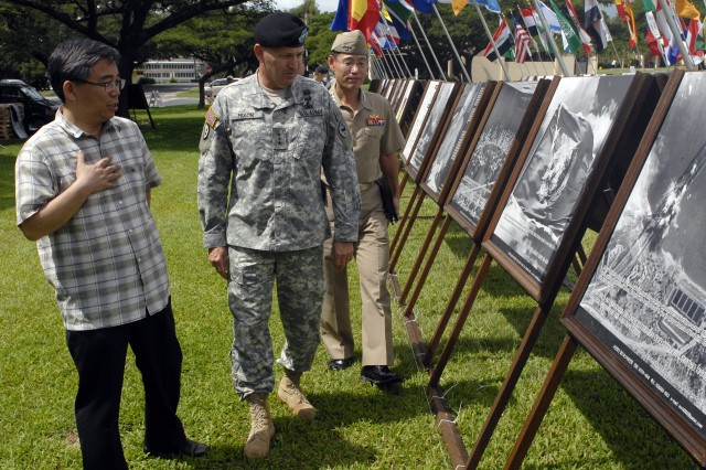 """Lt. Gen. Benjamin R. Mixon (center), U.S. Army Pacific commander, tours a pictorial history of the Korean War Feb. 23 at Fort Shafter, Hawaii.  He was accompanied by Republic of Korea Navy Captain Hong Beom Hur (right), the Republic of Korea's defense attache to Hawaii. Their guide was Jaechul """"Benedict"""" Ahn, who created the exhibit and brought it to Hawaii. Ahn is chairman of The World Peace Freedom United, an organization based in the Republic of Korea. The exhibit moves Feb. 25 to Fort DeRussy in Waikiki and will be open to the public."""
