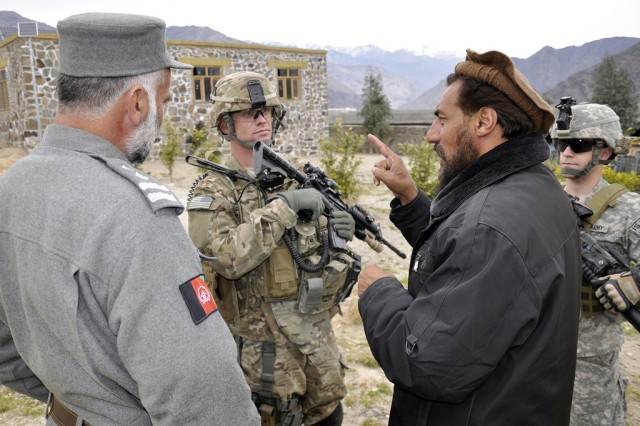 Capt. Garrett Gingrich (2nd from left), the commander of Charlie Company, 1st Battalion, 133rd Infantry Regiment, and a member of the Afghan National Security Forces, speak with Mehirulla Muslim (2nd from right), the Nurgaram district sub-governor, at the Nangaresh girls' school in the Nurgaram district of Nuristan, Afghanistan, Feb. 21, 2011. Gingrich represented Forward Operating Base Kalagush during a grand opening ceremony for a completed solar panel project.