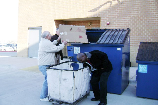 (Left to right) Bill Williams and Darron Cole from Killeen Independent School District place cardboard into one of the recycle dumpsters at Meadows Elementary School. The Fort Hood Recycle Center and KISD have formed a partnership in which the garrison will provide recycle services to the schools.