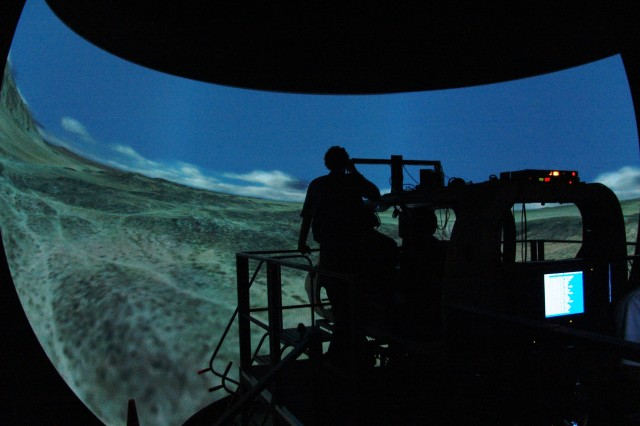 Technicians prep crewmembers in a simulated armed reconnaisance helicopter cockpit prior to testing on the virtual battlefield in the Battlefield Highly Immersive Virtual Environment Lab, or BHIVE Lab.