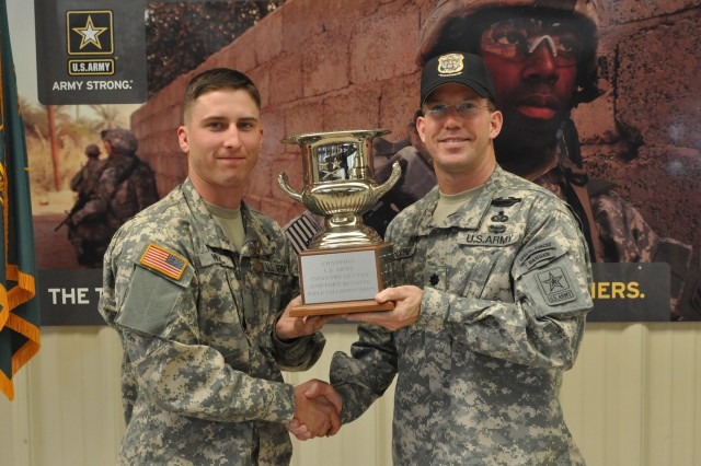 FORT BENNING, Ga. -- Lt. Col. Daniel Hodne, commander, U.S. Army Marksmanship Unit, presents Cadet Robert Hull, North Georgia College and State University, with the trophy for overall individual champion of the Maneuver Center of Excellence Combat Rifle Championship Feb 24 at Phillips Range. Hull, a corporal in the Georgia National Guard, dominated the field, winning the Excellence-in-Competition match as well as earning the coveted bronze Distinguished Rifle Badge during the match.  (Photo by Michael Molinaro, USAMU PAO)