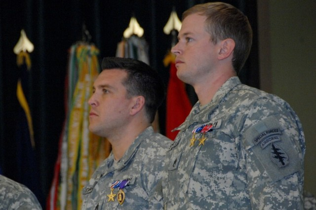 Staff Sgt Grant Derrick (left) and Staff Sgt. Justin Schafer (right), 3rd Battalion, 3rd Special Forces Group (Airborne), receive the Silver Star during a ceremony held at the John F. Kennedy Auditorium, Fort Bragg, N.C., for their gallantry in action against enemies forces while serving in Afghanistan in support of Operation Enduring Freedom.