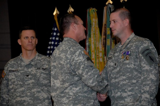 Maj. Gen. Kurt Fuller, deputy commanding general for U.S. Army Special Operations Command, congratulates Chief Warrant Officer 2 Jason Myers, 3rd Battalion, 3rd Special Forces Group (Airborne) after presenting him with the Silver Star for his heroism on the battlefield, during a ceremony at the John F. Kennedy Auditorium, Fort Bragg, N.C.