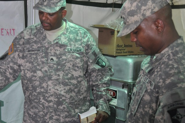 Staff Sgt. Alex Thibodeaux (left) assists Sgt. Joe Daniels (right) in preparing the grill on the MKT for the breakfast at Milan Army Ammunition Plant on Feb. 23, 2011.