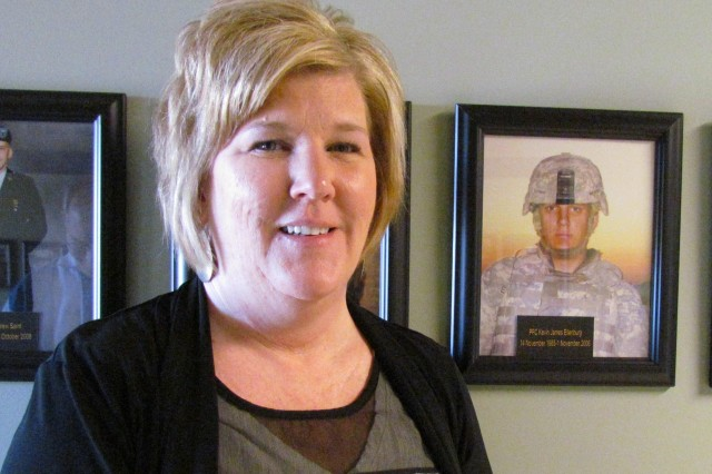 Julie Nethery stands with the picture of her son in the Hall of Remembrance at the Survivor Outreach Services facility at Redstone Arsenal, Ala. Pfc. Kevin Ellenburg was killed Nov. 1, 2006, when the Bradley armored fighting vehicle he was driving ran over two buried 500-pound improvised explosive devices that were detonated by remote control by the enemy in Baghdad, Iraq.