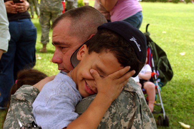 A Soldier with the 2nd Battalion, 35th Infantry Regiment, 3rd Brigade Combat Team, 25th Infantry Division, hugs his son before deploying in support of Operation Iraqi Freedom, in 2006.