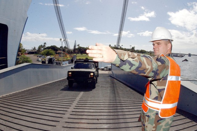 A maintenance noncommissioned officer with 545th Transportation Detachment, 25th Infantry Division, ground-guides an Army vehicle up a ramp to the USNS Pililaau on Ford Island, in 2003.
