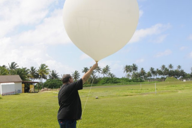 Mark Bradford, the lead meteorologist at Kwajalein, prepares a weather balloon and sensor to launch into the atmosphere. He and his team conduct two such launches every day.