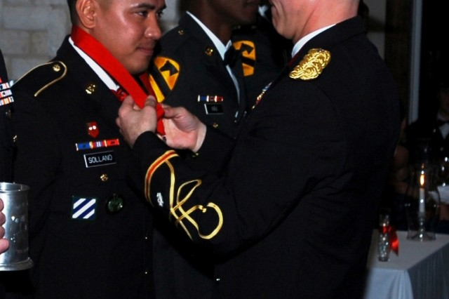 BELTON, Texas - Lt. Col. Nate Cook (right), commander of the 3rd Battalion, 82nd Field Artillery Regiment, 2nd Brigade Combat Team, 1st Cavalry Division, awards Sgt. 1st Class Anthony Sollano, a platoon sergeant with A Battery, 3rd Bn., 82nd FA Regt., the Honorable Order of St. Barbara during the St. Barbara's Day Ball in Belton, Texas Feb. 25.