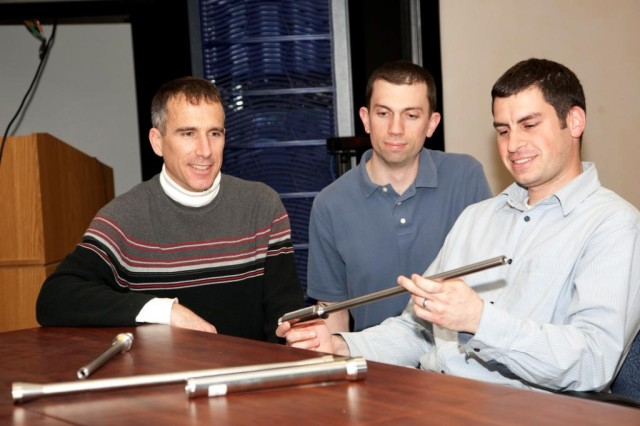 Far right, engineer Vinny Leto holds one of the various cobalt alloy barrels produced using the flow forming technique. The shortest barrel was the first produced, followed by full length barrels without rifling and later a prototype with rifling like the one that was tested. Other team members, from left, Michael Hespos and Keith Koehler.