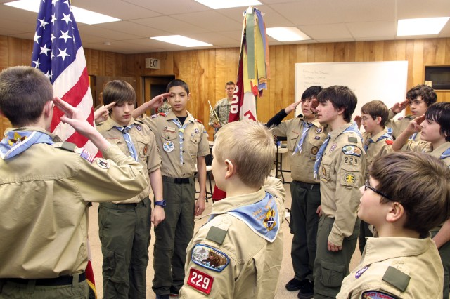 """EAGLE RIVER, Alaska -- Members of Boy Scout Troop 229 recite """"The Pledge of Allegiance"""" with members of U.S. Army Alaska's 9th Army Band before their Scout meeting. The Army musicians gave the Scouts a music appreciation presentation and familiarized them with instruments from the band's brass section here Feb. 24."""