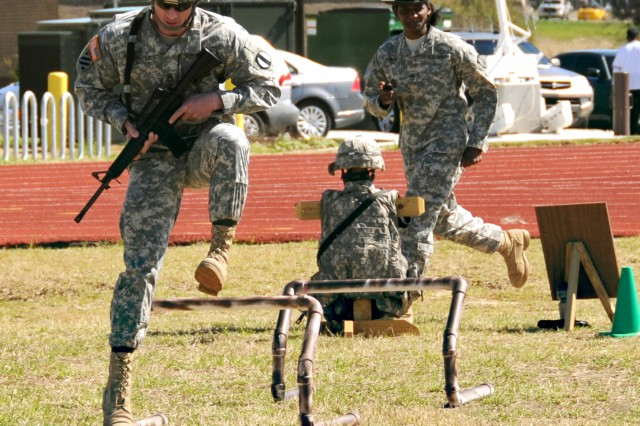 A Soldier high-steps over obstacles on the second leg of the new Army Combat Readiness Test after completing the first portion of the test, the 400-meter run.