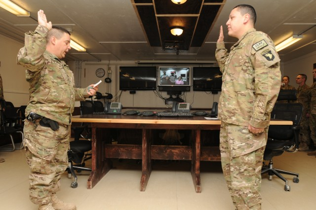 Maj. Raymond Delucio (left), 159th Combat Aviation Brigade communications officer, leads the newly promoted Sgt. 1st Class Juan Corral, brigade automations Non-Commissioned Officer in charge through the reaffirmation of the Oath of Enlistment at Kandahar Airfield March 2. Corral was promoted and reaffirmed his oath over a video teleconference that allowed his family to participate in the ceremony despite the fact that they were at Fort Campbell, Ky.