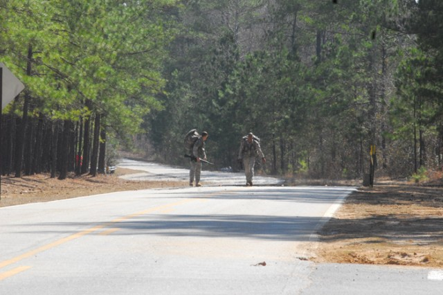 Staff Sgt. Thomas West and Master Sgt. Robert Carter, of 6th Ranger Training Battalion, outpace other teams in mile nine of a 12-mile road march Wednesday.