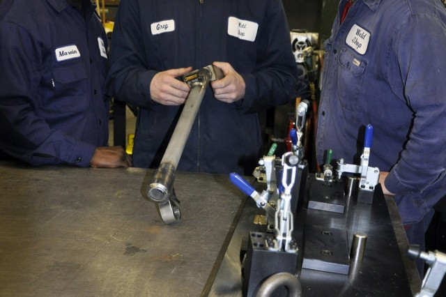 Lead welder Greg Stone, center, inspects a support leg for a 120mm mortar.  Stone checks each weld on every product that his team works on.  Fellow welders, Marvin Hunter, left, and Rob Hadeka await the final verdict.