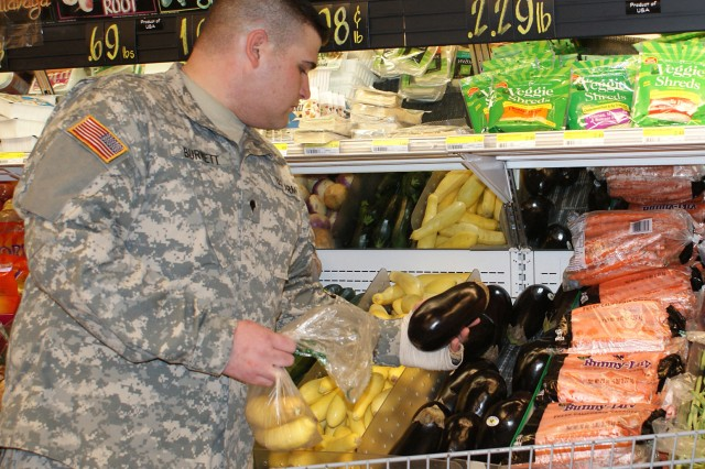 Spc. Logan Burnett picks out eggplant during a recent shopping trip at Fort Hood's Clear Creek Commissary. Burnett, a victim of the Nov. 5 shootings, now wants to come on active duty and is following nutrition advice from the CRDAMC dietitians in his struggle to meet Army standards for weight.