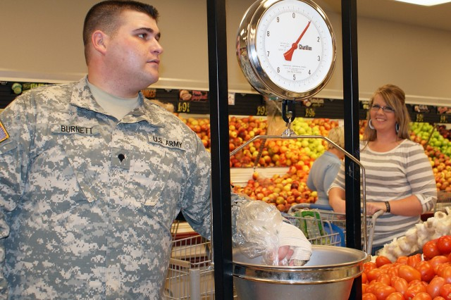 Spc. Logan Burnett weighs tomatoes he selected during a recent shopping trip with his wife, Victoria, at Fort Hood's Clear Creek Commissary. Burnett, a victim of the Nov. 5 shootings, now wants to come on active duty and is following nutrition advice from the Carl R. Darnall Army Medical Center's  dietitians in his struggle to meet Army standards for weight.