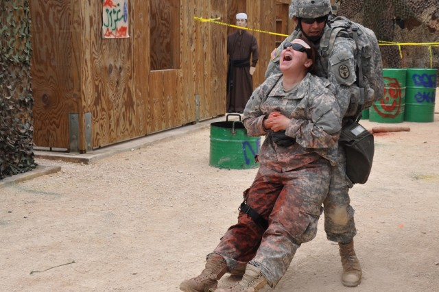 Spc. Jonathan Ruiz, from Martin Army Community Hospital, Fort Benning, Ga., must evacuate a simulated casualty using a one-person carry at part of the testing scenario on combat testing lane one during testing Feb. 23 at Camp Bullis, Texas.