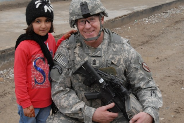 Command Sergeant Major Frank A. Grippe, the senior enlisted leader for the United States Central Command located at MacDill Air Force Base, Fla., poses with an Afghan child during a visit to the Kandahar City Police Headquarters in Afghanistan March 2.