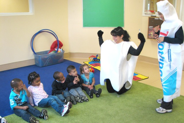 Lawrence Joel Troop Medical Clinic (LJTMC) registered dental hygienist Lorraine Lobos (dressed as a tooth), teaches children in the Child Development Center (CDC) preschool 1 class what it takes to have strong teeth during a visit Feb. 25. Lobos, assisted by LJTMC dental assistant Spc. Myrna Marcucci (dressed as a tube of toothpaste), visited CDC classes and Child, Youth and Schools Services (CYSS) prekindergarten (pre-K) class as part of Dental Awareness Month.