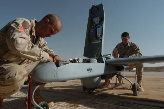 Spc. Robert Clarno and Spc. Jeremy Squires perform maintenance on a Shadow following the unmanned aerial vehicle's flight at Forward Operating Base Warhorse, Iraq.