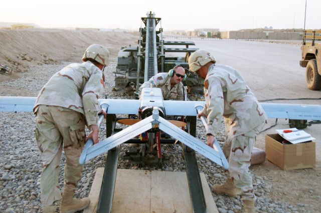 "Soldiers in Iraq prepare RQ-7B Shadow 200 for launch from a trailer-mounted pneumatic catapult. The ""R"" is the Department of Defense designation for reconnaissance while ""Q"" means unmanned aircraft system, ""7"" refers to it being the seventh of a series of purpose-built unmanned reconnaissance aircraft systems and ""B"" represents improvements over the previous A model."