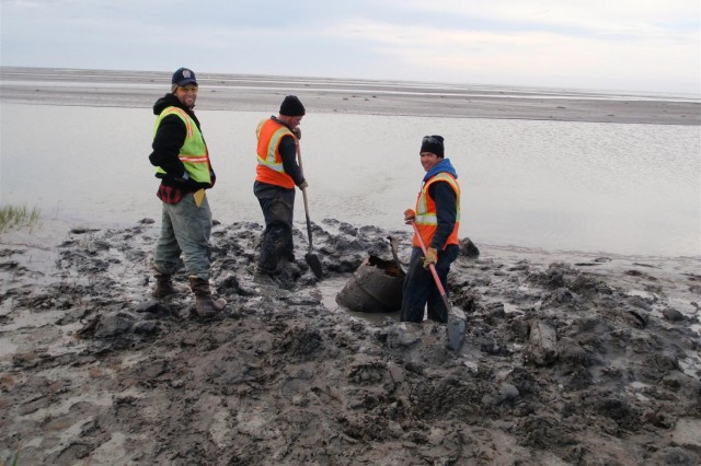 Sam Widmer (left) with Weston Solutions works with Eric Jenks (center), and Mike Flisk (right) with Marsh Creek, LLC to retrieve a buried drum from a sand bar in the Jago River delta.  Over 1,400 drums were recovered from the Jago River area.