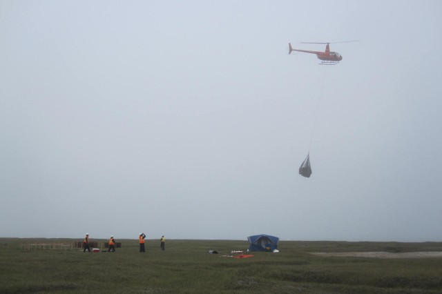 Workers from Marsh Creek and Weston Solutions observe a sling load of 8-10 drums being transported by a Pollux Aviation R-44 helicopter to Kaktovik, Alaska.