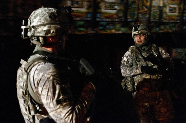 Staff Sgt. Kevin J. Stanfield (left), a platoon sergeant, and Spc. Damian C. Caldino, a food service specialist, both assigned to Forward Support Company G, 2nd Battalion, 320th Field Artillery Regiment, Task Force Balls, 1st Brigade Combat Team, 101st Airborne Division, pull security as Jinga trucks pass behind them, during a recent convoy in eastern Afghanistan, Feb. 28.