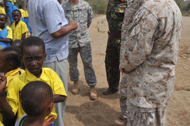 Kenyan and American military members speak with Joseph Gilong, head teacher at Kauthara Primary School in the Coastal School District, during five weeks of civil-military operations training in Manda Bay, Kenya.