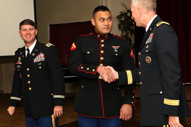 Marine of the Year, Lance Cpl Robert Toilolo, Marine Corps Detachment, Fort Huachuca shakes hands with  Brig. Gen. Gregg Potter, commander, U.S. Army Intelligence Center of Excellence and Fort Huachuca while Col. Timothy Faulkner, U.S. Army Garrison commander, Fort Huachuca looks on during the Installation Awards Banquet, Friday night at the Thunder Mountain Activity Centre.
